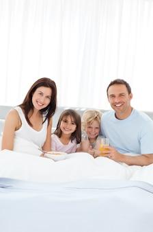 ベッドで両親と朝食をしている兄弟と姉妹