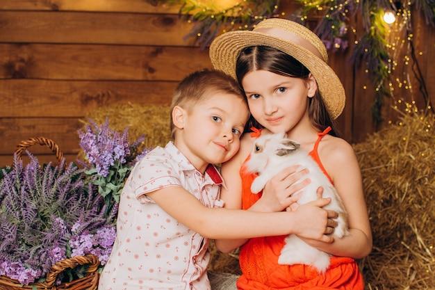 행복한 형제와 자매는 건초 위에 있는 마을에서 토끼를 껴안습니다
