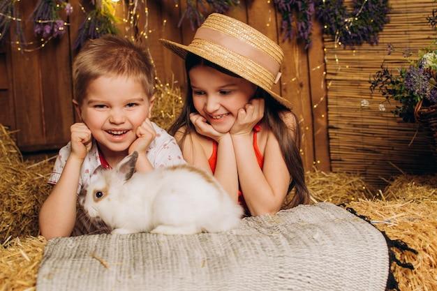 행복한 형제와 자매는 건초 위에 있는 마을에서 토끼를 껴안습니다.