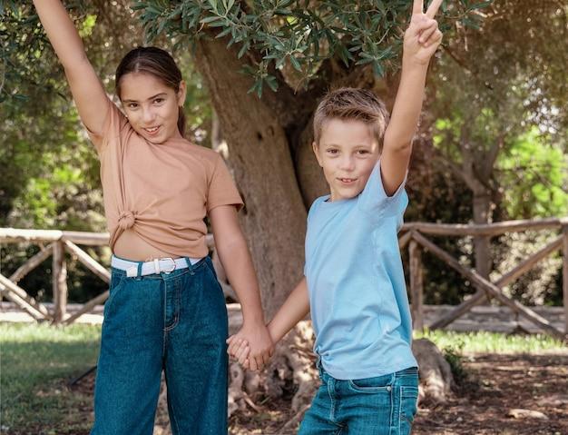 Счастливые брат и сестра держат друг друга за руки и показывают жест v на открытом воздухе. симпатичные детские девочка и мальчик, весело проводящие время в парке летом. макет футболки