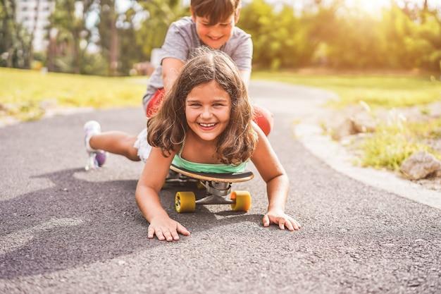 Счастливый брат и сестра, играя с longboard на открытом воздухе
