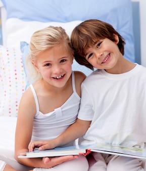 Счастливый брат и сестра читает книгу в спальне