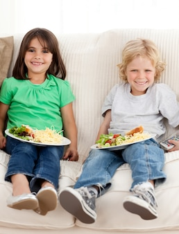 파스타를 먹는 동안 텔레비전을보고 행복 형제와 자매