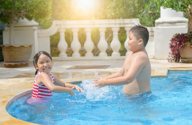 Happy brother and sister play in swimming pool,