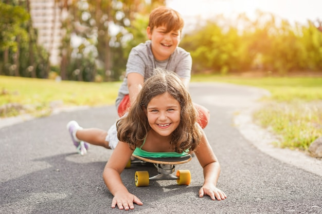 Happy brother and sister playing with longboard outdoor - young people having fun in summer time outside