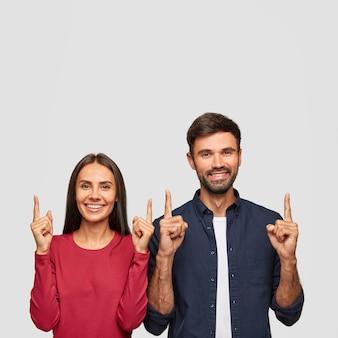 Fratello e sorella felici sorridono ampiamente, attirano la tua attenzione verso l'alto, suggeriscono o consigliano di salire le scale