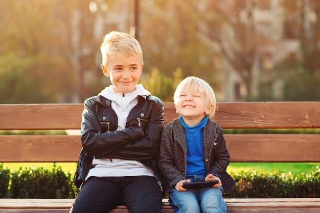 屋外で一緒に楽しんで幸せな兄弟。電話を使用してゲームをプレイする小さな男の子。幸せな寒気。家族と子供の関係