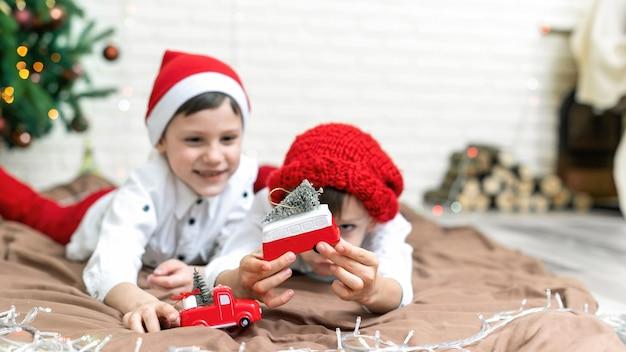 クリスマスの衣装を着た幸せな兄弟が、自宅のクリスマスツリーの近くの床で遊んでいます。幸せな家族のアイデア
