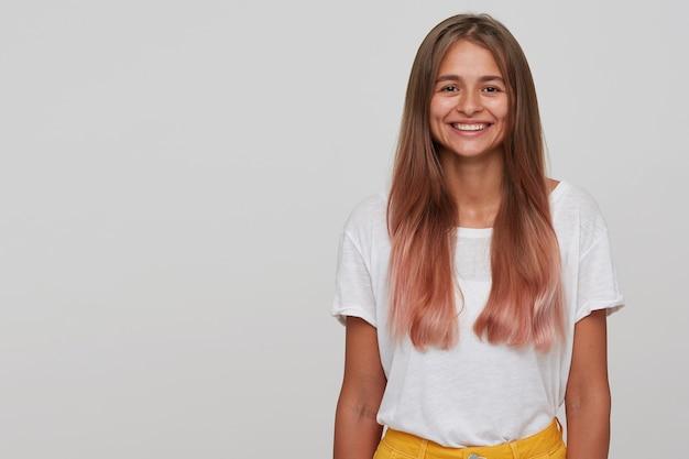 흰 벽 위에 포즈를 취하는 동안 매력적인 넓은 미소로 유쾌하게 보이는 흰색 기본 티셔츠를 입은 행복한 갈색 눈의 젊은 긴 머리 금발 여성