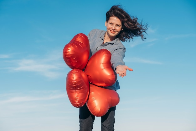 Happy brunet woman holding heart-shaped balloons on the beach on valentines day.