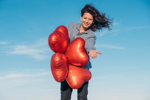 Счастливая брюнетка женщина, держащая воздушные шары в форме сердца на пляже в день святого валентина.