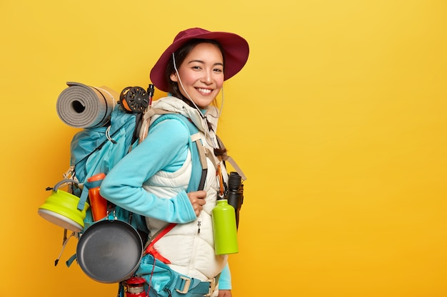 Happy brunette asian traveler carries big tourist backpack, uses binoculars for journey, stands against yellow wall, wears stylish hat, jumper with vest