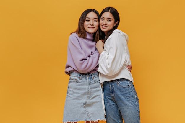 Felice donna asiatica bruna in gonna di jeans e maglione viola abbraccia un amico
