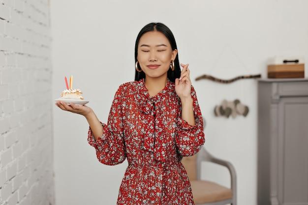 Felice donna asiatica bruna in abito floreale esprime un desiderio e tiene in mano un gustoso pezzo di torta di compleanno birthday