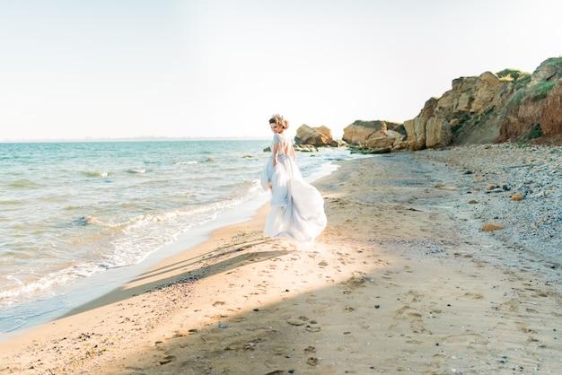 海の近くでポーズをとるビーズで刺繍された軽いシフォンのウェディングドレスの幸せなブルネットの花嫁。