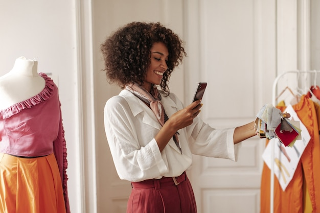 Happy brunette curly excited woman in white stylish blouse and burgundy pants holds phone, smiles and takes photo of textile samples