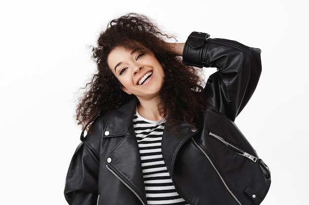 黒のジャケットと幸せなブルネットの巻き毛の女性