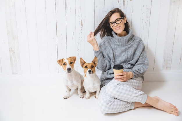 Happy brunette female dressed in loose domestic clothes, spends time with dogs