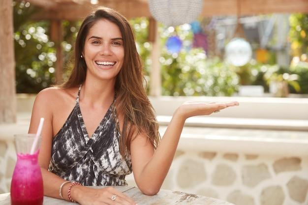 Счастливая женщина брюнетка наслаждается счастливыми днями отпуска, сидит в кафе отеля, демонстрирует прекрасные апартаменты, пьет коктейль из свежих фруктов. привлекательная молодая женщина кавказа отдыхает в курортной стране
