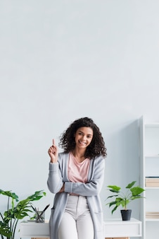 Happy brunette female pointing up in workplace
