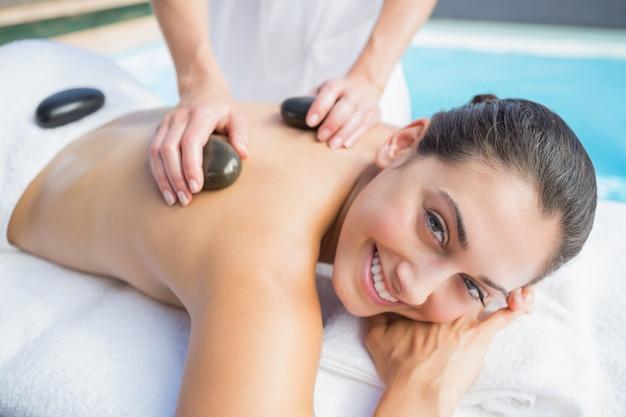 Happy brunette getting a hot stone massage poolside