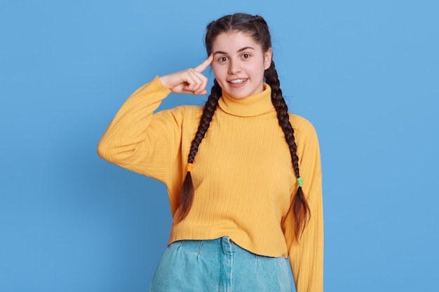 Happy brunette girl holds index finger on temple, tries to think before acting stupidly, smiles happily, dressed in casual sweater and jeans, stands against blue wall