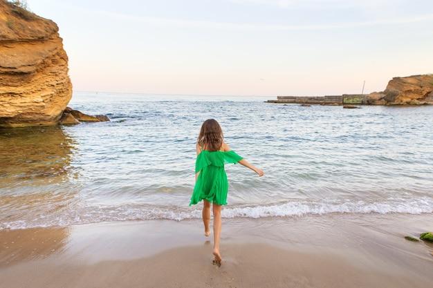 Счастливая девушка брюнетка в зеленом платье бежит к морю. красивый закат.