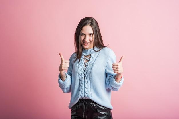 Счастливая девушка брюнет показывает палец вверх, жест согласия. в студии на розовом фоне