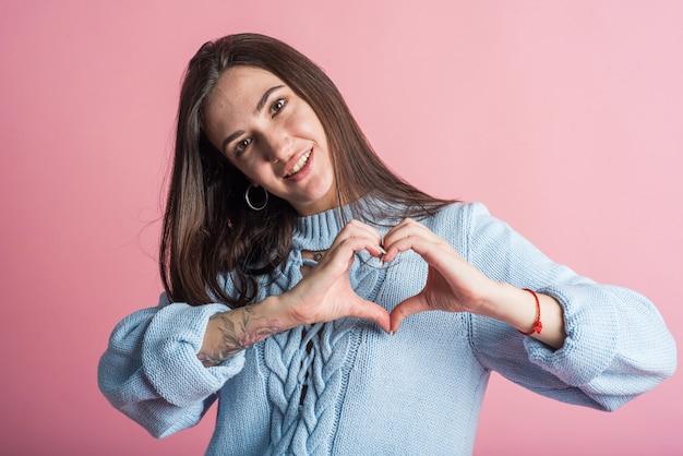 Счастливая девушка брюнет показывает жест любви, знак сердца. в студии на розовом фоне