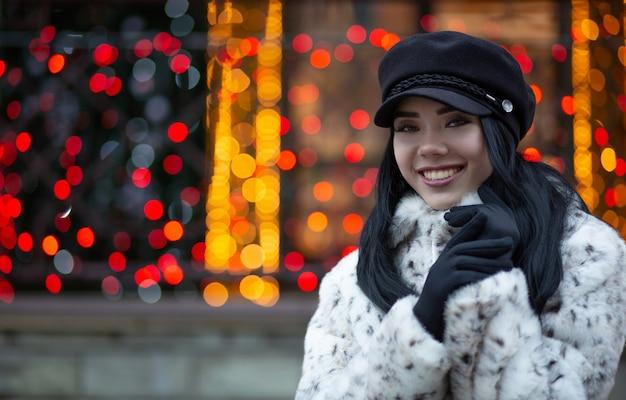ボケと花輪の背景の上の通りでポーズをとって帽子をかぶって幸せなブルネットの少女。テキスト用のスペース