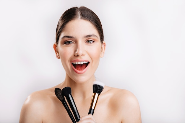 Happy brunette girl without makeup smiling, holding makeup brushes on white wall.