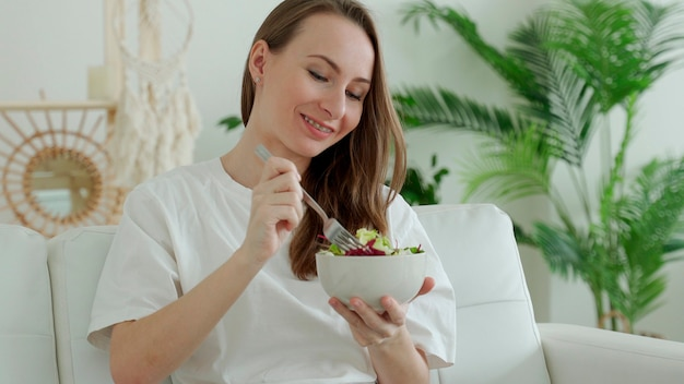 Счастливая брюнетка отдыхает на диване и ест овощной салат дома.