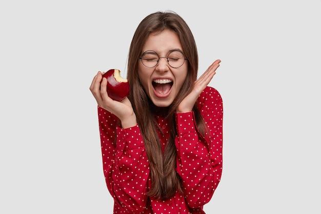 Счастливая брюнетка восклицает и активно жестикулирует, кусает свежее яблоко, держит глаза закрытыми, наслаждается здоровым питанием