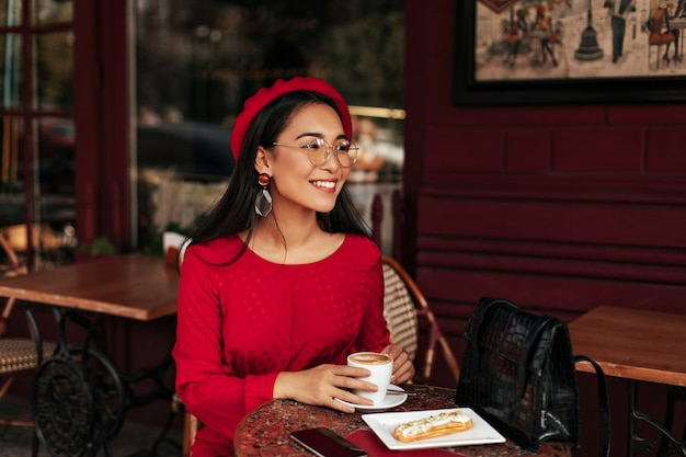 Happy brunette lady in red dress and beret smiles sincerely