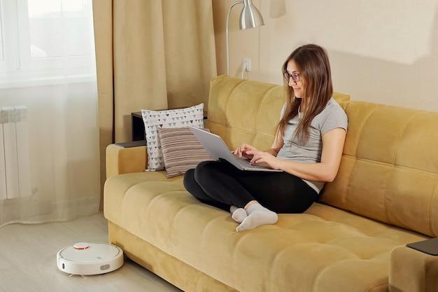 眼鏡をかけた幸せなブルネットの女性は、快適なソファに座っているラップトップを使用し、現代のロボット掃除機はリビングルームの床を掃除します