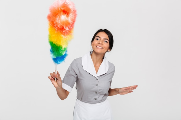 Happy brunette maid in gray uniform swipe with duster