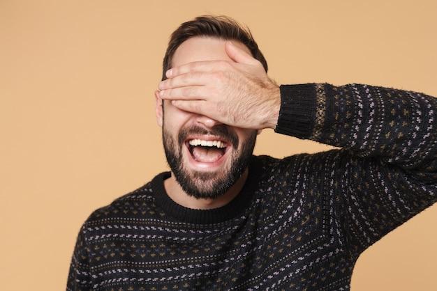 Счастливый брюнет в зимнем свитере смеется и закрывает глаза руками, изолированными над бежевой стеной