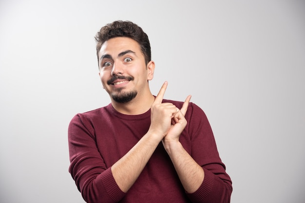 A happy brunette man posing with his hands .