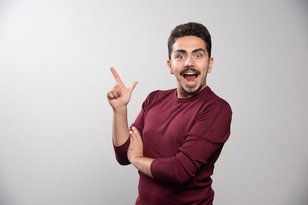 Un uomo castana felice che mostra un dito e in posa.