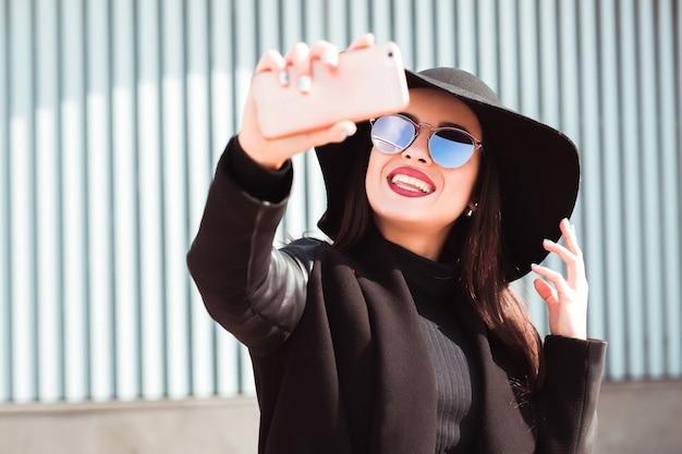 携帯電話で自分撮りをしている幸せなブルネットモデル。女性は帽子とサングラスを着用します