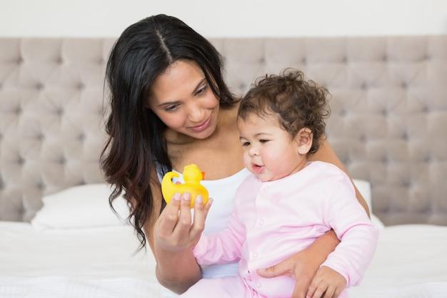 Happy brunette showing yellow duck to her baby in bedroom