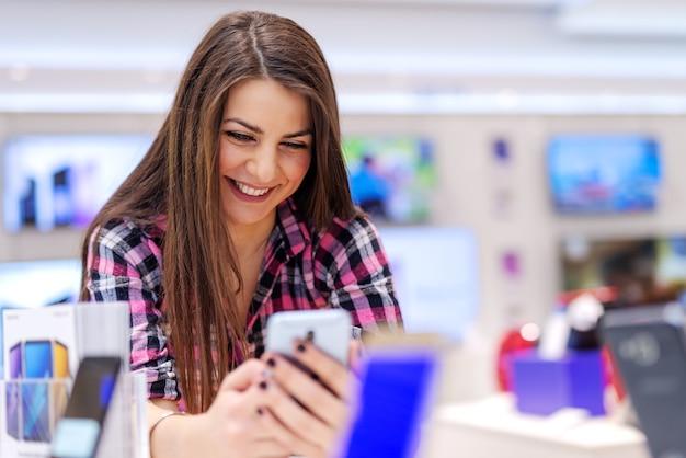 Счастливая брюнетка стоит в техническом магазине и пробует смартфон, который хочет купить.