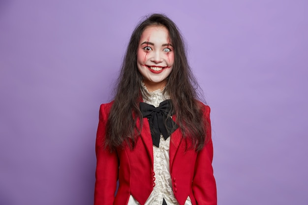 Happy brunette terrifying asian woman has spooky eyes with lenses and blood scars dressed in masquerade costume smiles positively isolated on vivid purple wall