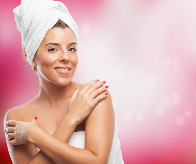 Happy brunette in towel on hair embracing herself