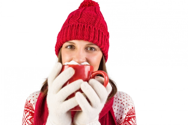 Happy brunette in winter clothes holding mug