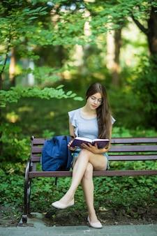 公園のベンチに座っている手にノートブックと幸せなブルネット