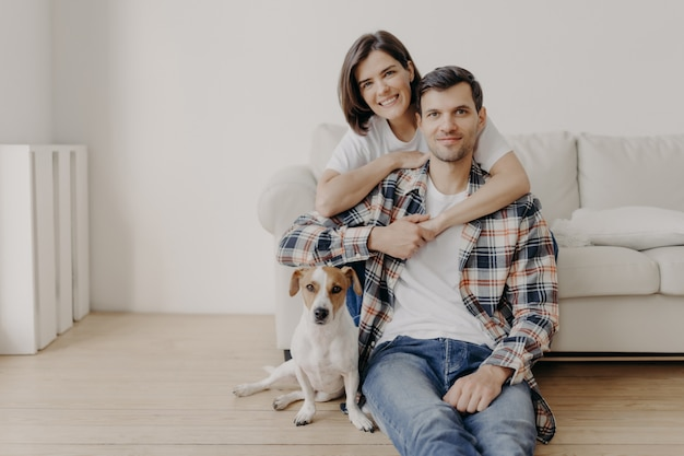 Happy brunette woman embraces husband with love, being in good mood, smiles positively. husband, wife and dog pose together in living room of new dwelling, enjoy comfort. couple in love indoor