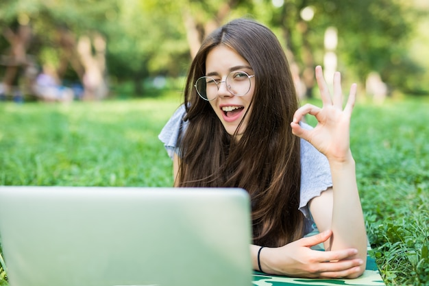 Happy brunette woman in eyeglasses lying on grass in park with laptop computer and showing ok sign