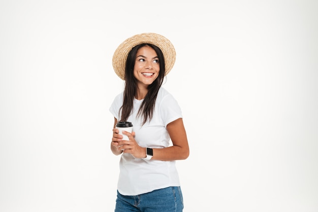 Happy brunette woman in hat holding take away coffee cup