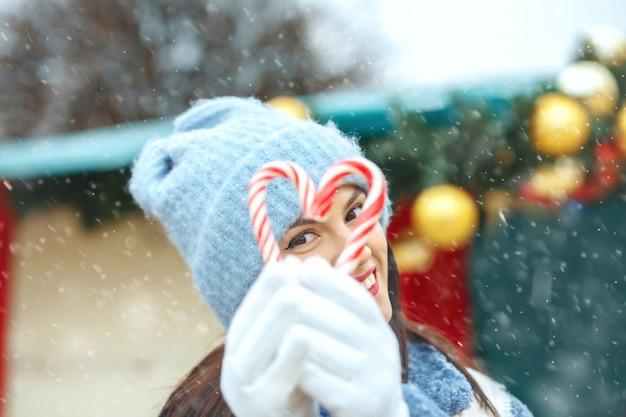 降雪時にハートの形でキャンディーを保持している幸せなブルネットの女性
